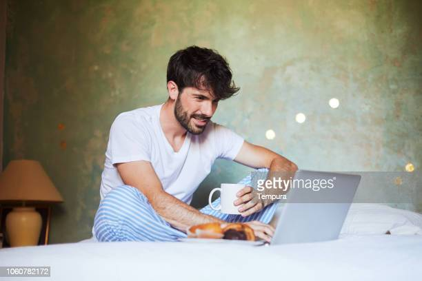 young man working with laptop in bed. - pajamas stock pictures, royalty-free photos & images