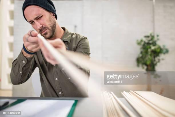 young man working with wood at desk in office - designer einrichtung stock-fotos und bilder