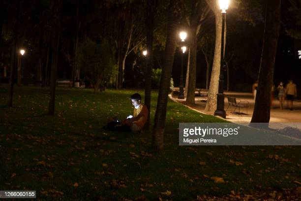 Young man works on his computer at night in the Debod Temple park on August 20 in Madrid, Spain.