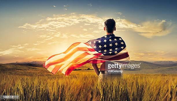 jovem homem envolto bandeira americana recorte campo ao pôr-do-sol - patriotismo - fotografias e filmes do acervo