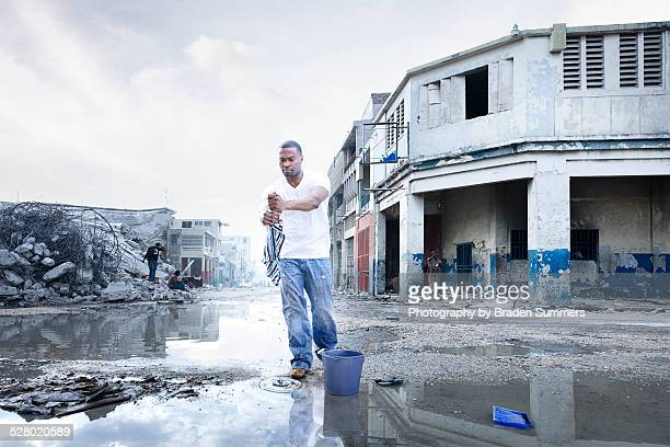 Young man wringing out rag in Port au Prince