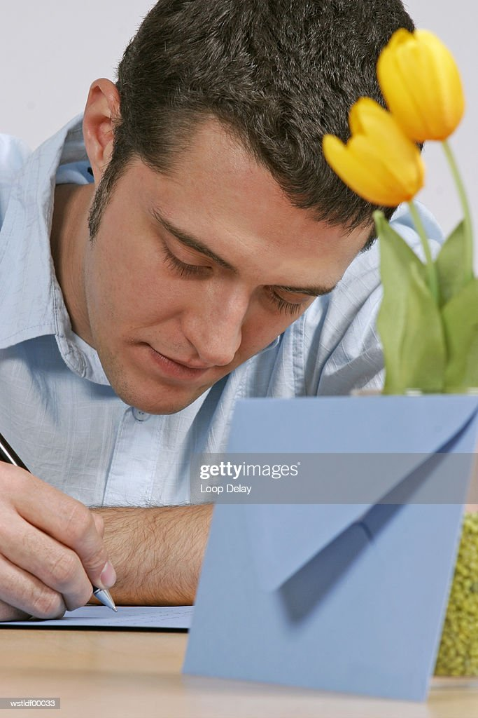 Young man writing a letter : Stock Photo