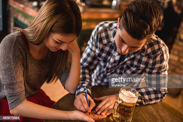 young man writing his phone number on woman's hand. - telephone number stock pictures, royalty-free photos & images
