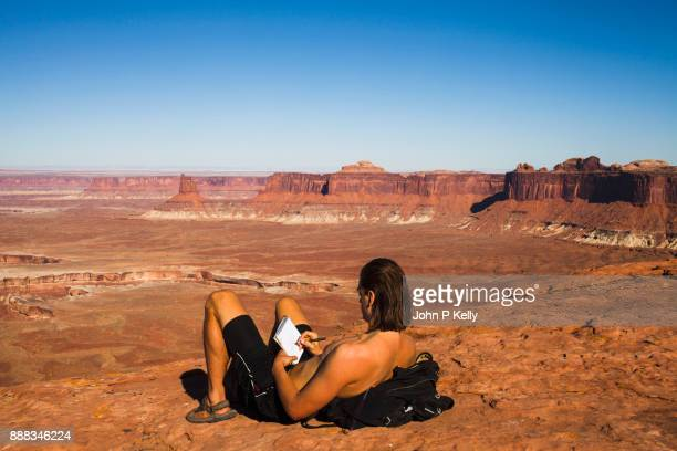 Young man writing in his journal looking out at Canyonlands National Park