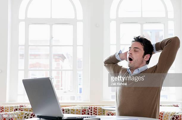Young man yawning at office
