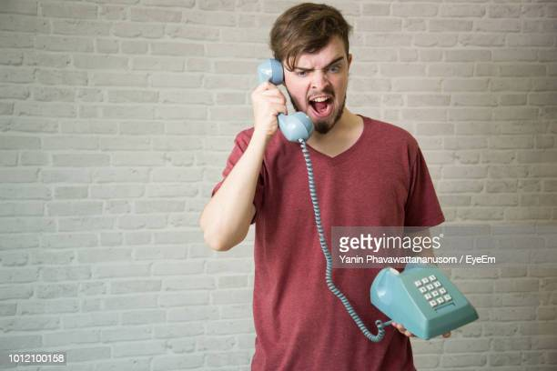 Young Man Yawning While Using Telephone Against Brick Wall