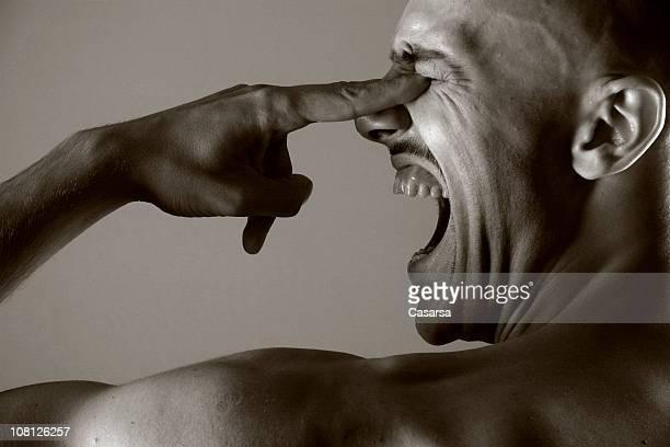 Junger Mann mit schreien und Stochern sich in die Augen, Sepia