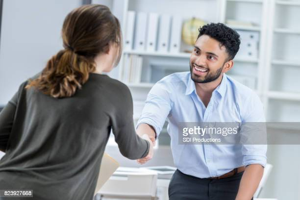 young manager greets prospective employee before interview - social grace stock pictures, royalty-free photos & images