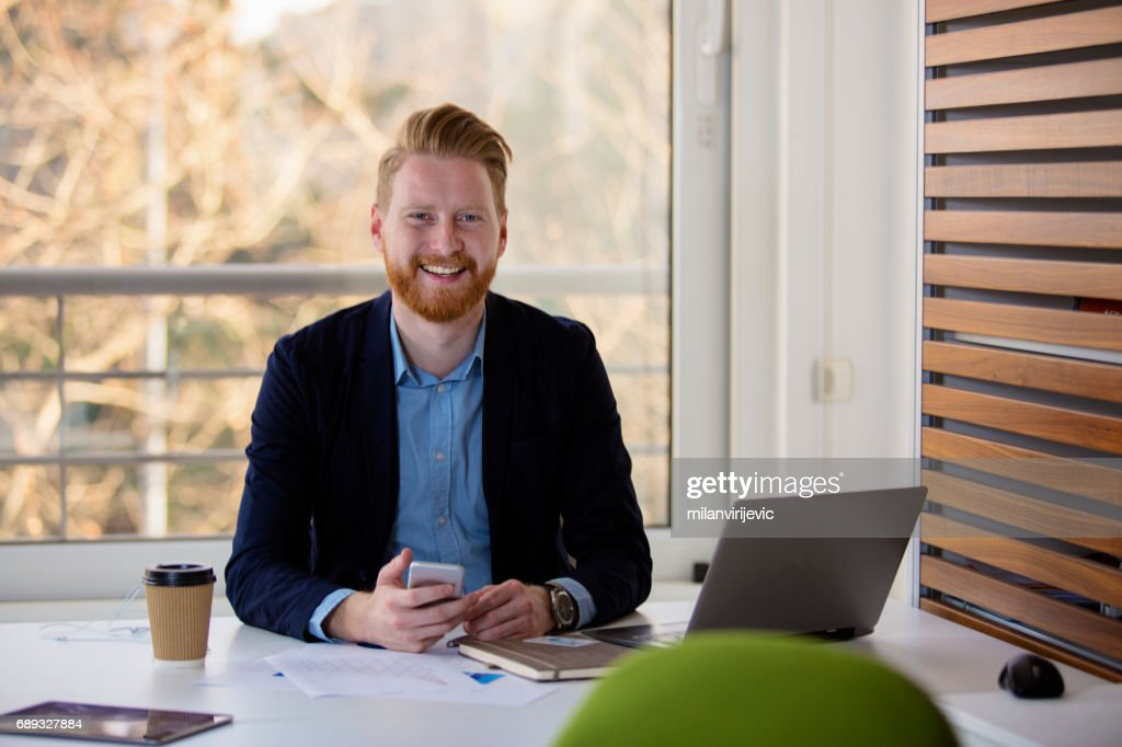 Young manager smiling in his office : Stock Photo