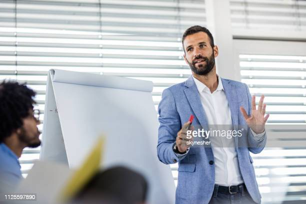 young manager talking on a business presentation in a board room. - presenter stock pictures, royalty-free photos & images