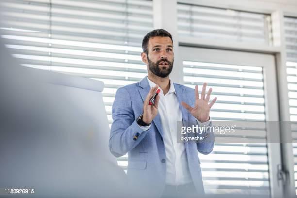 young manager talking on a business presentation in a board room. - apresentador imagens e fotografias de stock