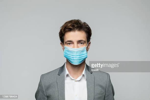 young manager wearing protective face mask - suit stock pictures, royalty-free photos & images