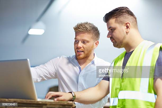 Young manager working with foreman in factory