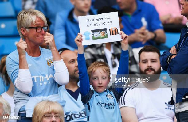 A young Manchester City fan shows off his banner during the Premier League match between Manchester City and Hull City at Etihad Stadium on April 8...
