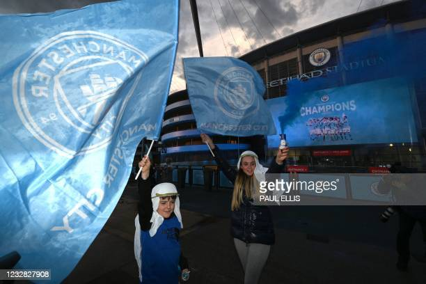Young Manchester City fans celebrate their club winning the Premier League title, outside the Etihad Stadium in Manchester, north west England, on...