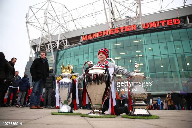 A young Manchester United fan pose for a photo with replicas of the Premier League Trophy The UEFA Champions League Trophy and the FA Cup Trophy...