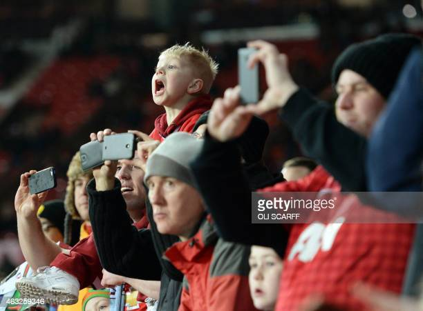 A young Manchester United fan shouts out to the players as they warmup prior to the English Premier League football match between Manchester United...