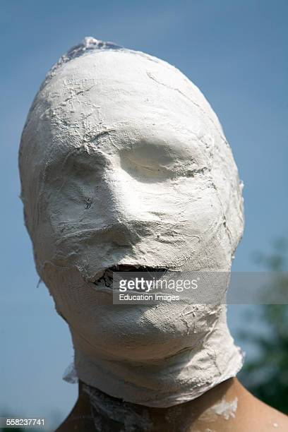 Young man's face covered in white bandage tape as art project