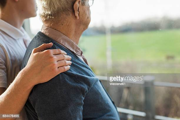 young man's hand on the shoulder of a senior man - hand auf der schulter stock-fotos und bilder