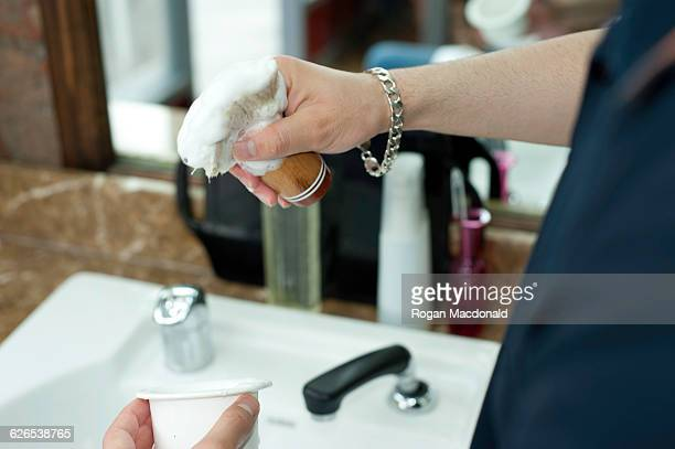 Young mans hands lathering shaving cream on shaving brush