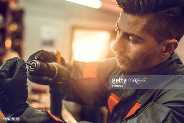 Young manual worker adjusting screw on an electrical drill.