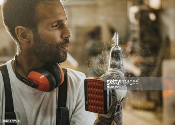 Junge Arbeiter bläst Sägemehl aus einem Bohrer.