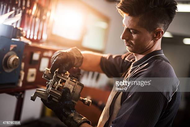 young manual worker repairing electric motor in a workshop. - electric motor stock photos and pictures