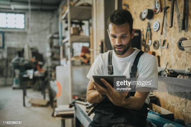young manual worker using digital tablet in a workshop. - craftsperson stock pictures, royalty-free photos & images