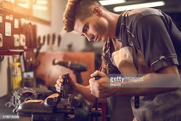 Jeune Travailleur manuel en travaillant sur un serre-joint à l'atelier.