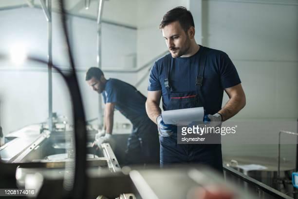 junge arbeiterin, die in einer fabrik an papierarbeiten arbeitet. - maschinenbau stock-fotos und bilder