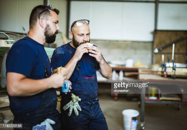 young manual workers eating sandwiches on a break in a workshop. - lunch break stock pictures, royalty-free photos & images