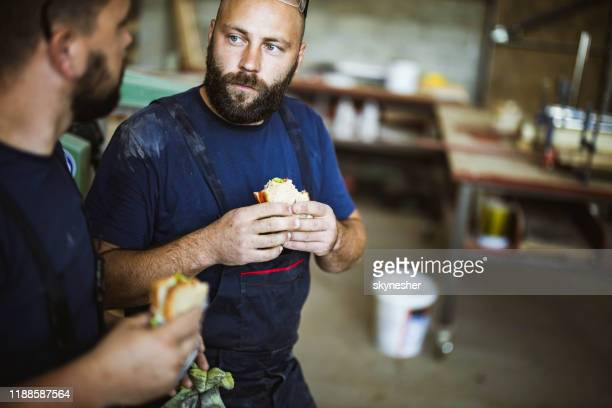 jonge arbeiders praten terwijl ze broodjes eten tijdens een pauze in een workshop. - pauze nemen stockfoto's en -beelden