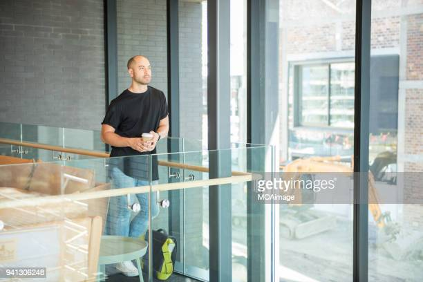 A young Maori and Caucasian mixed man is standing by the window