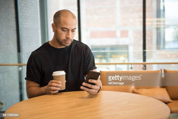 A young Maori and Caucasian mixed man is using his cellphone