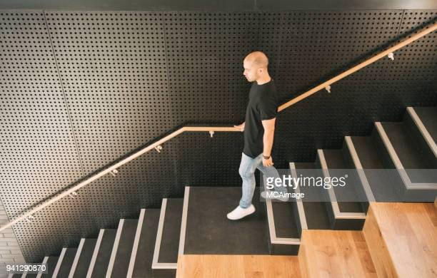 A young Maori and Caucasian mixed man is walking down the stairs