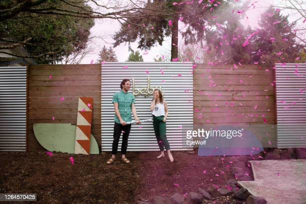 a young married couple celebrate the gender of their baby at a gender reveal party - annonce grossesse photos et images de collection