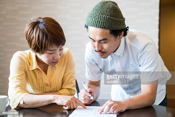 young married couple filling out important paper documents - form filling stock pictures, royalty-free photos & images
