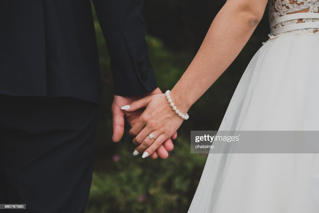 Young married couple holding hands : Stock Photo