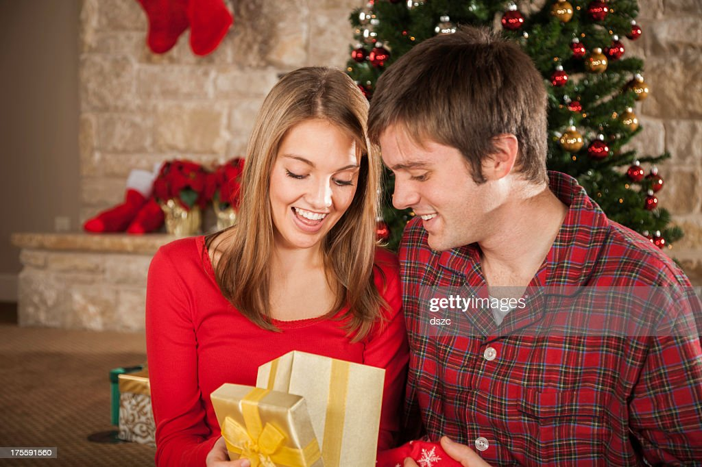 young married couple on christmas morning opening gift stock photo