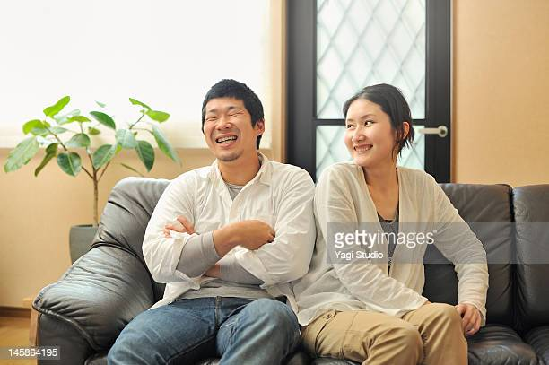 a young married couple sitting on a sofa in a livi - 夫婦 ストックフォトと画像