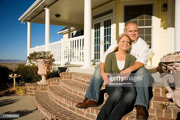 Young Married Couple Sitting on Front Steps at Home