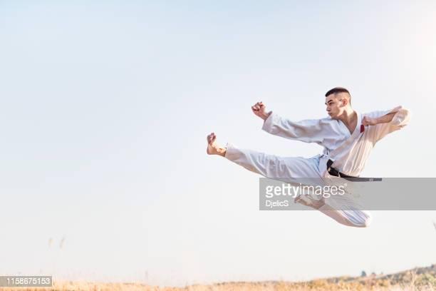 junge kampfsportler üben fliegende tritte in der natur. - treten stock-fotos und bilder