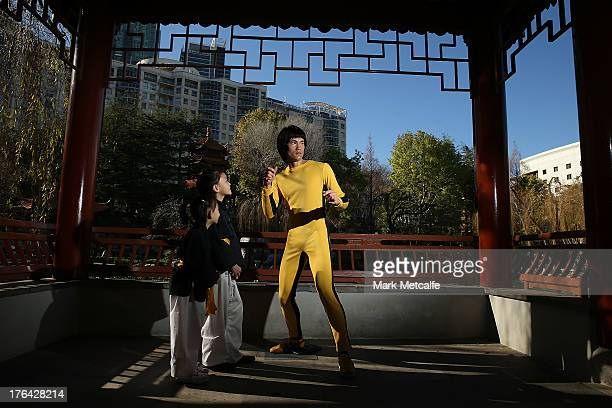 Young martial arts students pose alongside a wax figure of Chinese actor Bruce Lee at the Chinese Garden of Friendship on August 13 2013 in Sydney...