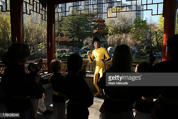 Young martial arts students pose alongside a wax figure of Chinese actor Bruce Lee at the Chinese Gardens on August 13 2013 in Sydney Australia The...