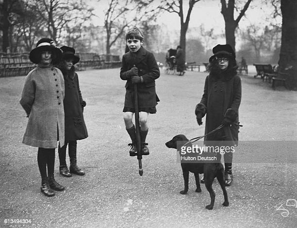 Young Martin Chateris bounces on a pogo stick during a trip to Hyde Park with friends