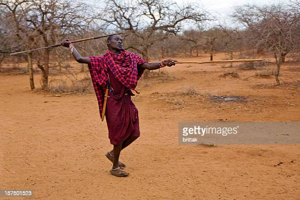 Young masai warrior throwing spear.