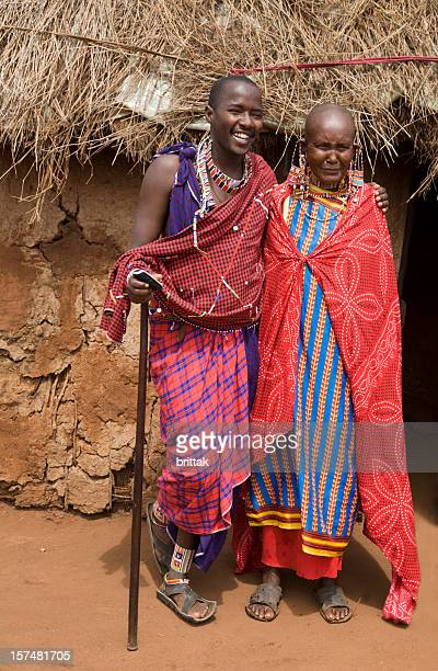 Young masai with old female relative outside her mud hut.
