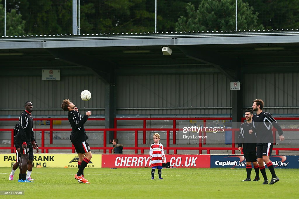 A young mascot warms-up with the players during the FA Cup Qualifying Third Round match between Kingstonian and Eastbourne Borough at The Cherry Red Records Stadium on October 12, 2014 in Kingston upon Thames, England.