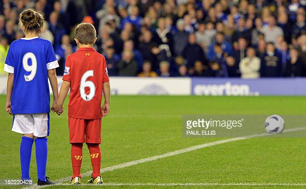 Young mascots wearing Liverpool and Everton football kits stand as players and supporters applaud the support of the Hillsborough familes ahead of...