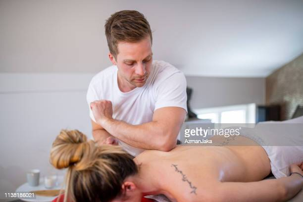young massage therapist massaging a woman - swedish culture stock pictures, royalty-free photos & images